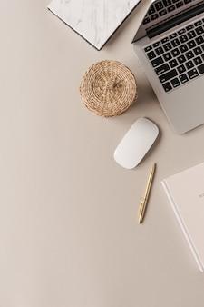 Рабочий стол домашнего офиса с ноутбуком, соломенной шкатулкой на нейтральном фоне. плоская планировка