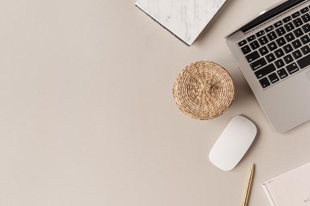 Рабочий стол домашнего офиса с компьтер-книжкой, соломенной шкатулкой на нейтрали. плоская планировка, вид сверху