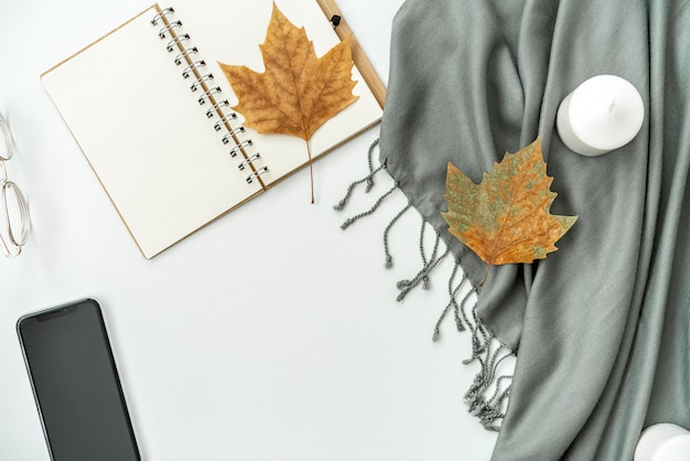 Home office desk workspace with mobile phone with blank black screen, notebook, maple leaves, candles on white