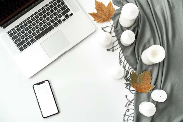 Home office desk workspace with mobile phone with blank white screen, laptop, notebook, scarf, candles, leafes on white Premium Photo
