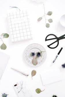 白い背景にペン、紙、ノート、ユーカリの枝を持つホーム オフィス デスク ワークスペース。上面図。