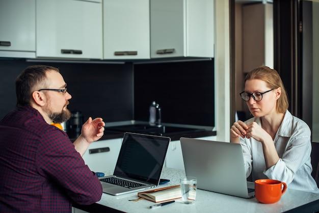 Домашний офис во время самоизоляции. муж и жена в очках сидят за столом на кухне, удаленно работают вместе на ноутбуках, обсуждают и улыбаются. семейный фрилансер.