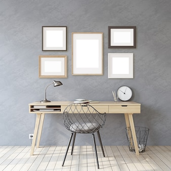 ホームオフィス。インテリアとフレームのモックアップ。灰色の壁の近くの木製の机。灰色の壁にさまざまな種類のフレーム。 3dレンダリング。