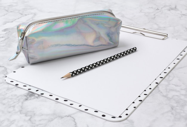 Home office marble desk with clipboard, holographic pencil case and pensil.