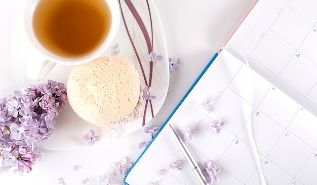 Home office: an open diary notebook with and lilac flowers on a desk with tea and biscuits
