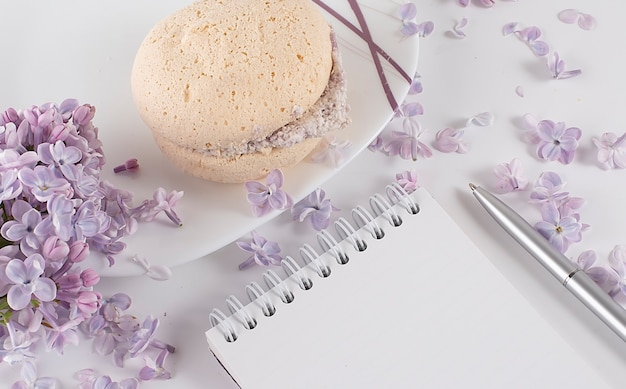 Home office: an open diary notebook with and lilac flowers on desk with tea and biscuits