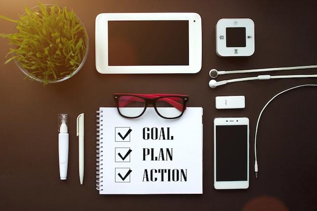 ホームオフィス。ヴィンテージ茶色の背景に白い文房具の要素のセットです。新年の目標、計画、オフィスアクセサリー付きのメモ帳のアクションテキスト。ビジネスの動機、インスピレーションの概念。