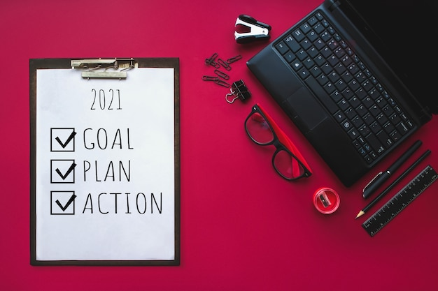 ホームオフィス。ヴィンテージの赤い背景に2021年の目標、計画、アクションのテキストと白い文房具の要素のセット。空白の文房具の写真。デザインのモックアップ。