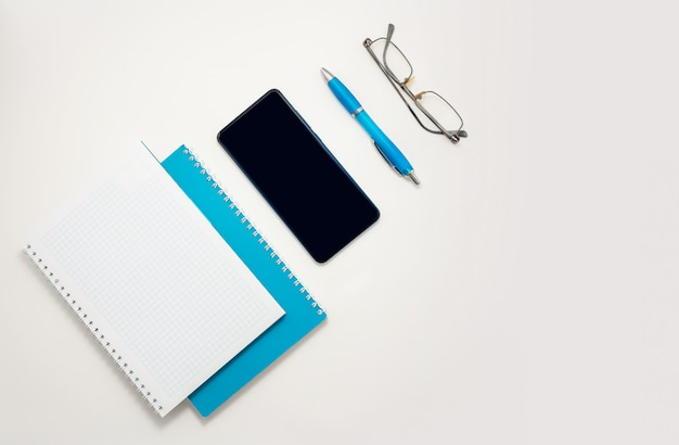Home office smartphone blue notebook glasses pen top view