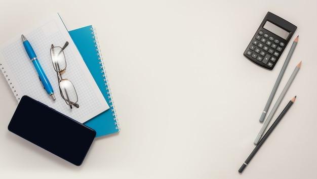 Home office smartphone blue notebook pencils pen top view