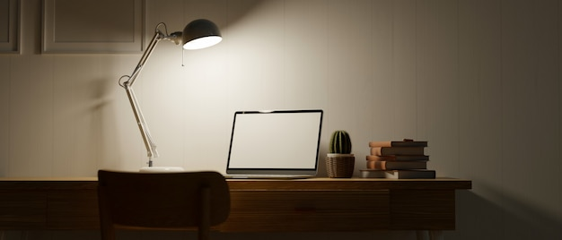 Home office space at night with low light tablet blank screen modern table lamp mock up frames