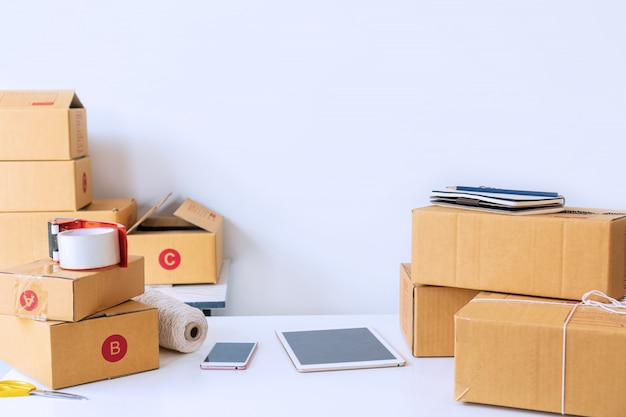 Home office of startup online business seller, showing table with cardboard boxes, tablet