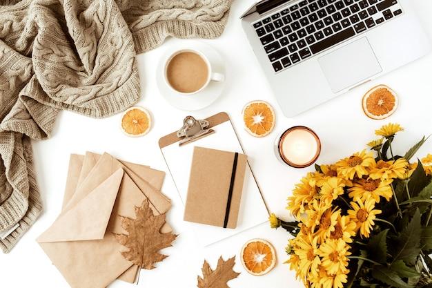 Рабочий стол для домашнего офиса с ноутбуком, украшенный букетом желтых ромашек, кофейная чашка, дольки апельсина, плед