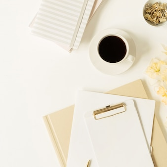 Home office table workspace. blank sheet clipboard pad with copy space, coffee cup, narcissus flowers, stationery on white