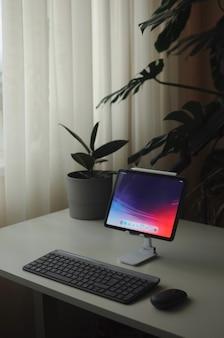 テーブルの上にタブレットデバイスを備えたホームオフィスミニマリズムスタイリッシュなインテリアインテリア植物と内部