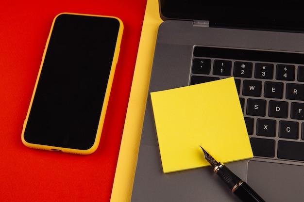 ホームオフィスワークプレイスデスクのコンセプト。ラップトップ、スマートフォン、ペン、赤い背景に黄色の付箋が付いています。