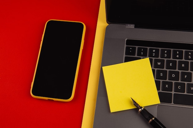 ホームオフィスワークプレイスデスクのコンセプト。ラップトップ、スマートフォン、赤い背景の付箋。