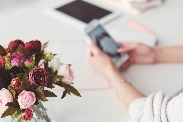 ホームオフィスの職場。個人的なスタイルと居心地のよさ。花の花束。スマートフォンを閲覧している女性。