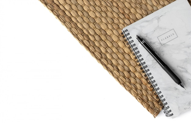Home office workspace background with notepad and straw napkin on white background