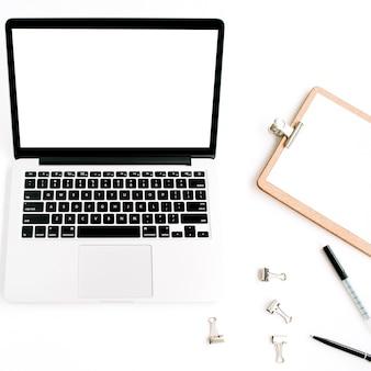 ホームオフィスのワークスペースのモックアップ。空白の画面、クリップボード、アクセサリを備えたノートパソコン