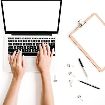 ホームオフィスのワークスペースのモックアップ。空白の画面、クリップボード、キーボードで入力する手を持つノートパソコン