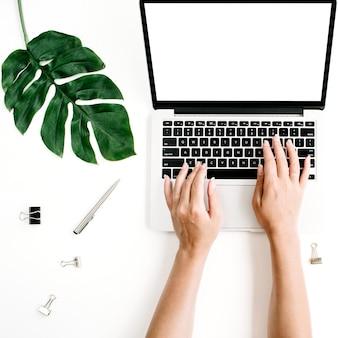 ホームオフィスのワークスペースのモックアップ。空白の画面、ヤシの葉、キーボードで入力する手を持つノートパソコン