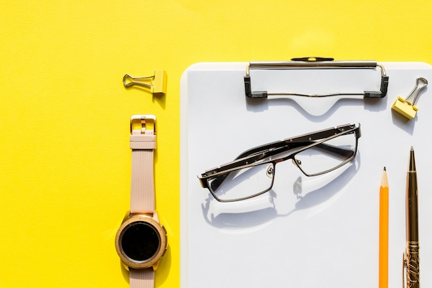 Home office workspace mockup with clipboard, watch ,glasses and accessories. check list, empty note paper on yellow wall. office, writer or study concept.template for blog, bloger, business