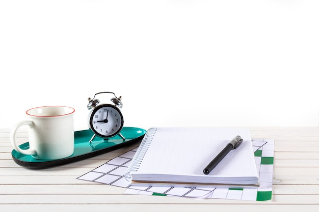 Home office workspace mockup with notebook, pen, cup of coffee, alarm clock on wooden desk