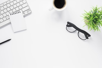 Home office workspace mockup with spiral notepad; keyboard; coffee; eyeglasses and plant