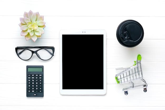 ホームオフィスのワークスペース。タブレット、グラス、電卓、トロリー、一杯のコーヒー、白い木製のテーブルに多肉。トップビューフリーランスの仕事、ビジネス、オンライン注文、貿易の概念