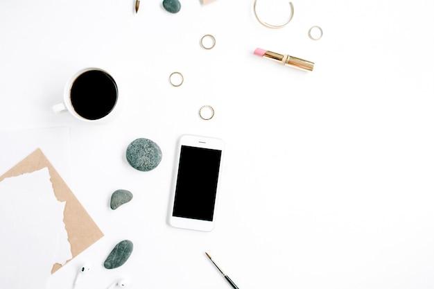 커피, 휴대 전화, 공예 봉투, 돌, 헤드폰 및 흰색 표면에 빈 종이가있는 홈 오피스 작업 공간