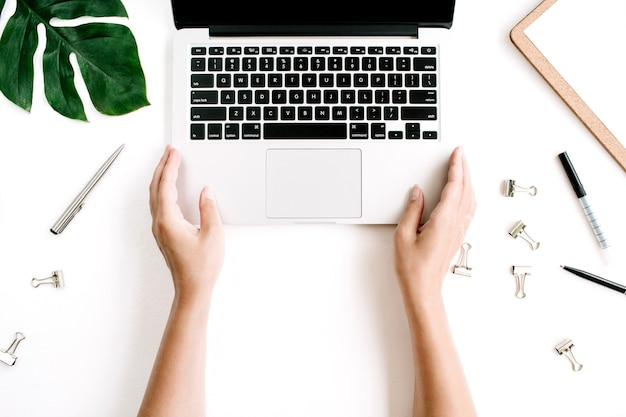 ノートパソコンのキーボードで作業する手でホームオフィスのワークスペース