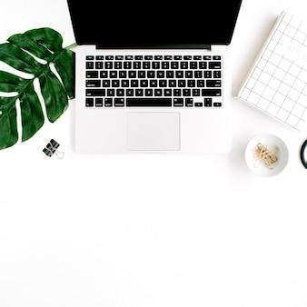 ノートパソコンとヤシの葉のあるホームオフィスのワークスペース