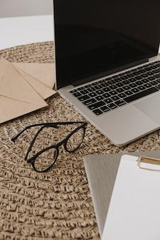ノートパソコン、メガネ、クリップボードパッド、封筒を備えたホームオフィスのワークスペース。