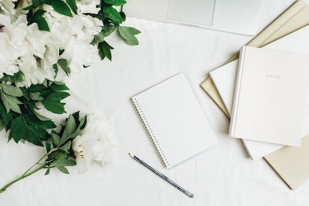 Home office workspace with laptop, notebook, white peonies flowers bouquet on white surface