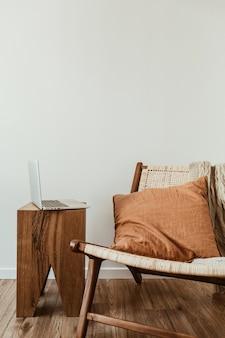 노트북과 홈 오피스 작업 공간. 세련된 등나무 나무 의자, 니트 격자 무늬, 생강 베개.