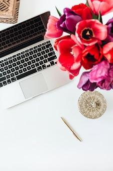 ノートパソコン、チューリップの花の花束とホームオフィスのワークスペース