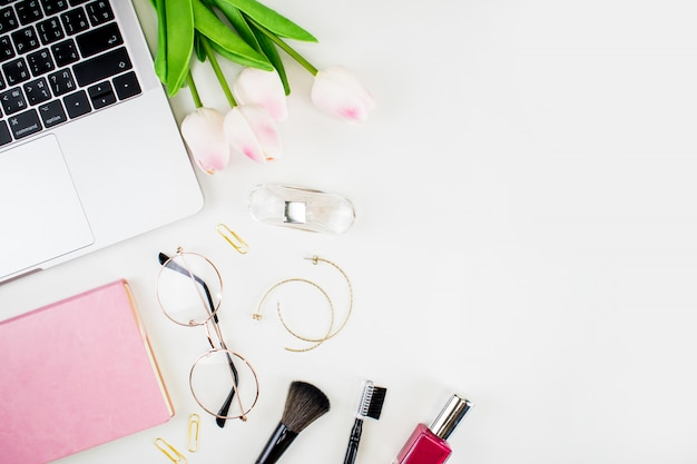 본사 작업 공간. 여성 패션. 장미, 노트북, 메이크업 브러쉬 및 흰색 배경에 액세서리의 꽃다발. 평평한 누워, 평면도 복사 공간.