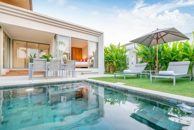 녹지 정원, 일광욕 침대, 우산, 수영장 수건이있는 열대 수영장 빌라를 보여주는 집 또는 집 외관 디자인 프리미엄 사진