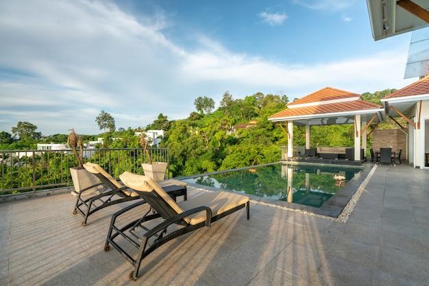 태양 침대와 열대 수영장 빌라를 보여주는 집이나 집 외관 디자인