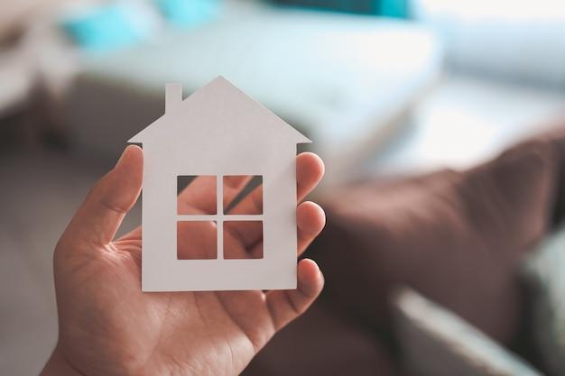 パステルカラーの部屋の背景の男の手に家や家のモデル。投資豊かな自由生活の概念