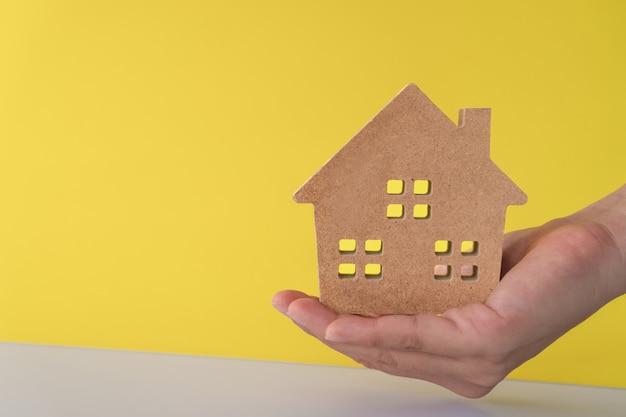 パステルカラーの部屋の壁で女性の手に家や家のモデル。投資裕福な自由生活のコンセプトです。
