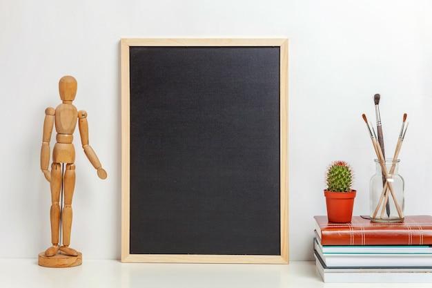 白い壁の近くのテーブルに空白の黒板をモックアップした家やオフィスの装飾。ミニマリズムインテリアワークプレイスアーティストは、装飾の背景を提供します。 hyggeスカンジナビアスタイルのワークスペースのコンセプト