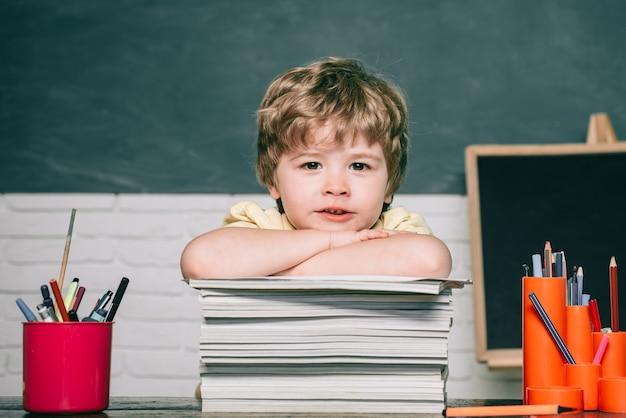 가정 또는 학교 교육. 초등학교에서 초상화 아이. 책을 가진 아이. 칠판 복사