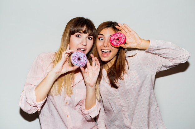 Home pajamas party. flash portrait of two funny women posing with donuts. surprise face.
