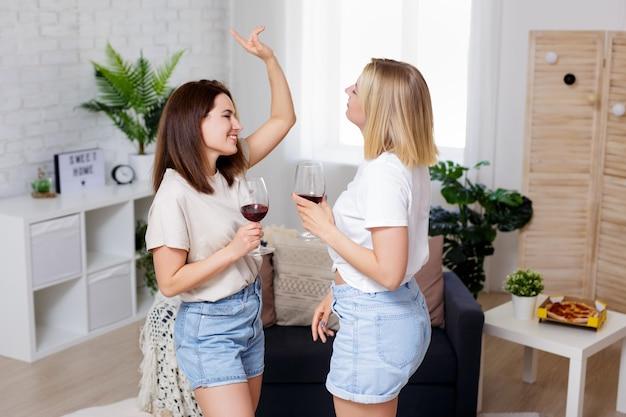 홈 파티 - 집에 있는 아늑한 거실에서 함께 즐거운 시간을 보내고 와인을 마시고 춤을 추는 두 명의 아름다운 소녀