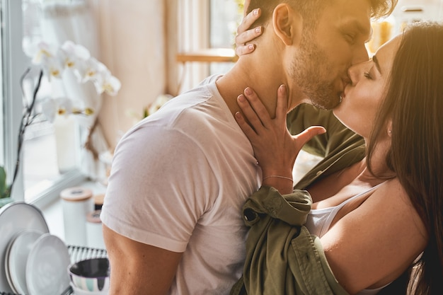 Home passion. pleased bearded man keeping his eyes closed while enjoying sweet kiss with his partner