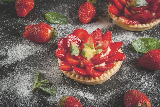 Home pies tartlets with custard and strawberries, decorated with mint and powdered sugar. on black stone table