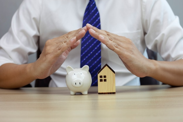 Home and piggy security concept insurance for real estate protecting gesture of man and house