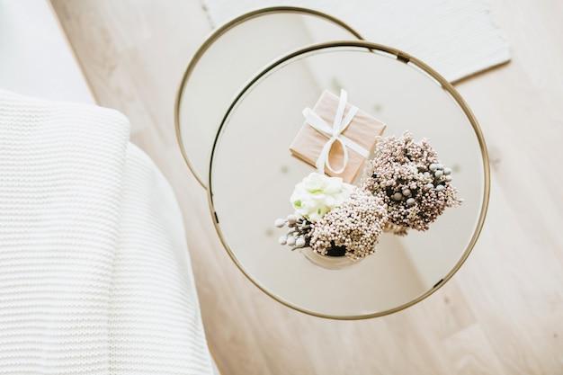 ガラスのコーヒーテーブルの上の家の植物の花とお祝いのギフトボックス。クリスマス、年末年始、冬休み